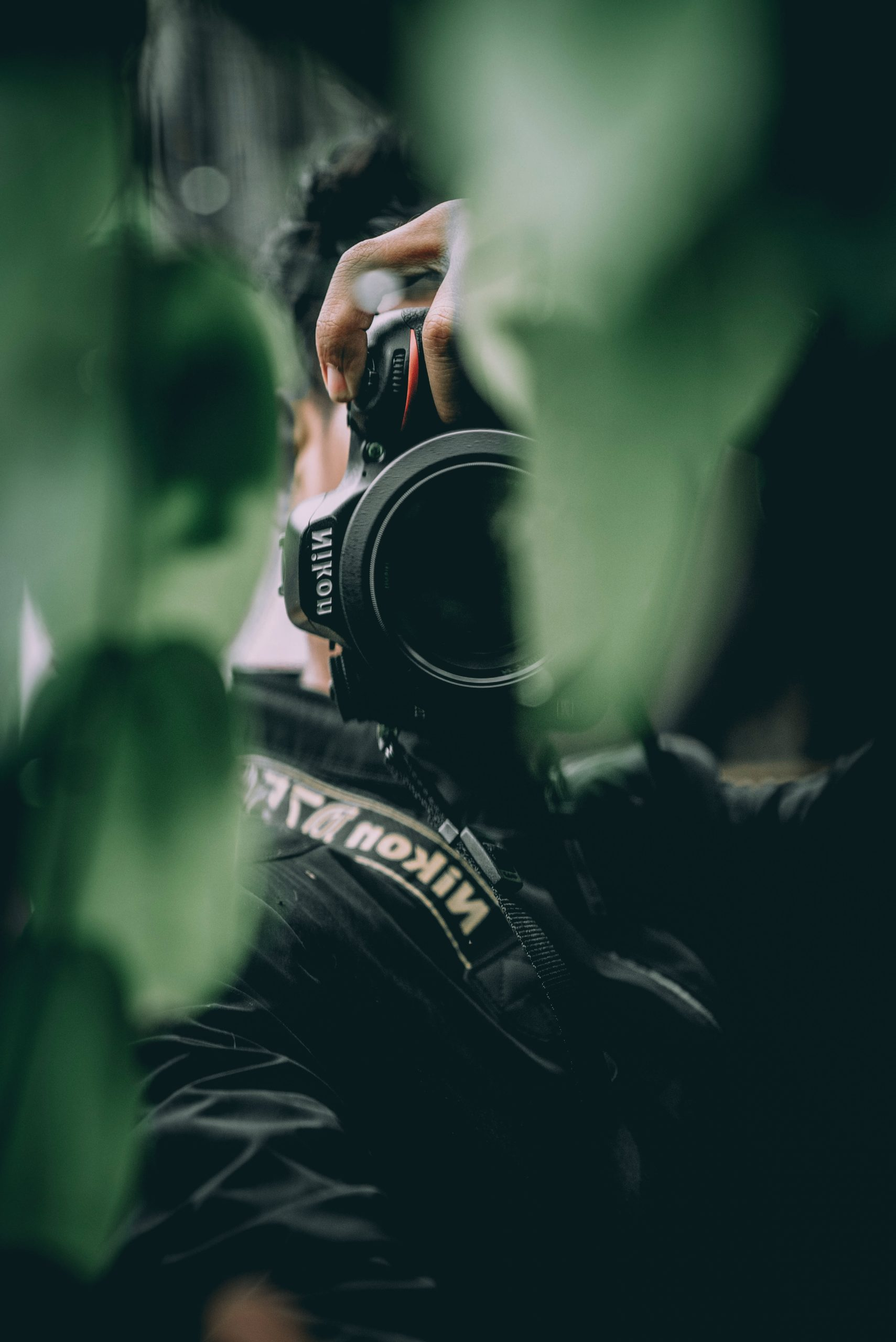 selective focus photography of person taking photo using DSLR camera