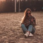 woman in blue denim jeans sitting on brown sand during daytime