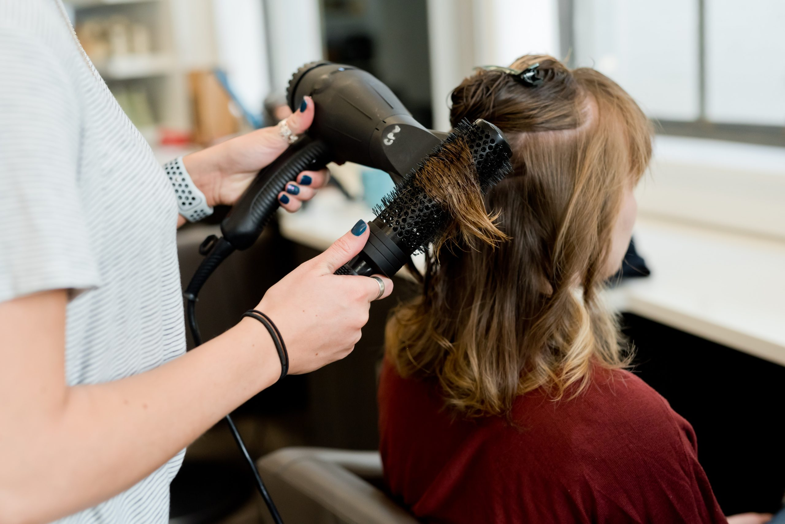 woman in red long sleeve shirt holding hair blower